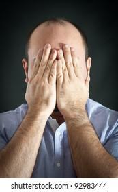 Man portrait with desperate expression on dark background.