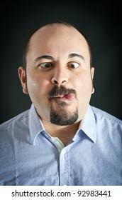 Man portrait with grimace expression on dark background.