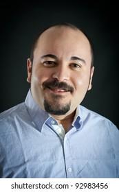 Man portrait with happy expression on dark background.