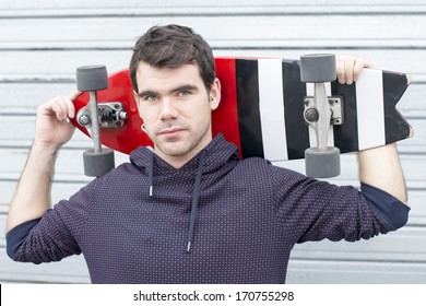 Man portrait holding skateboard on background.