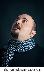Man portrait with hopeful expression on dark background.
