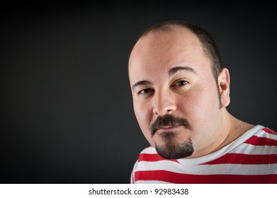 Man portrait with interdicted expression on dark background.