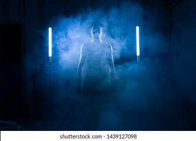 Man portrait posing with light of neon lamps and smoke over dramatic blue neon background in a dark room.