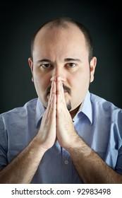 Man portrait with praying hands on dark background.