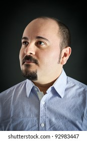 Man portrait with serene expression on dark background.