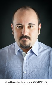 Man portrait with severe expression on dark background.