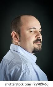 Man portrait with smart expression on dark background.