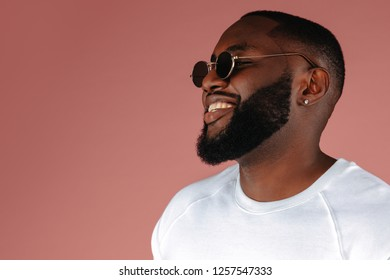 Man portrait. Style. Handsome African American guy in white T-shirt and sun glasses is smiling, on a pink background