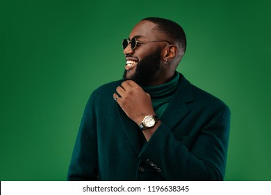 Man portrait. Style. Handsome Afro American guy in green jacket and sun glasses is smiling, on a green background