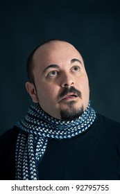 Man portrait with surprised expression on dark background.