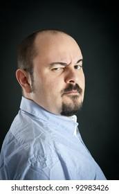 Man portrait with suspicious expression on dark background.