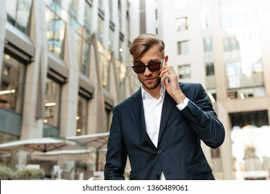 Man portrait. Technologies. Business. City style. Handsome businessman in suit and sun glasses is talking on the mobile phone while standing outdoors