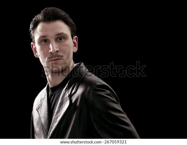 Man portrait wearing leather coat on black background