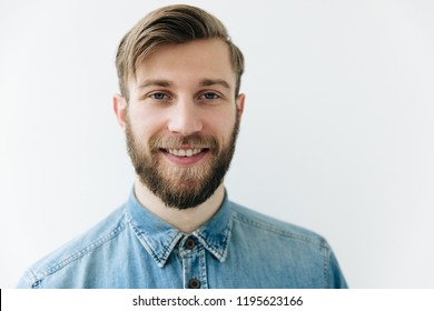 Man portrait. Young blond guy in jean shirt is looking at camera and smiling, on the white background