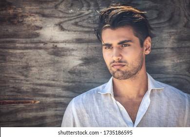 Ein Portrait von Mann, ein junges und gut aussehender Mann auf hölzernem Hintergrund. Er trägt ein weißes Hemd und hat einen leichten Bart.