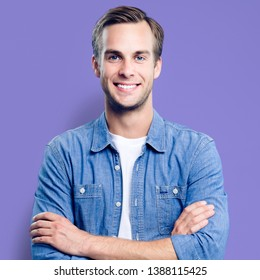 Man portrait. Young happy man with smiling face. Male model in blue shirt, crossed arms pose. Violet background. Guy in casual fashion clothing, studio photo. Square composition picture.