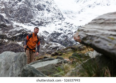 Man poses at the end of the glacier rocky trail wearing vest and having a pole.