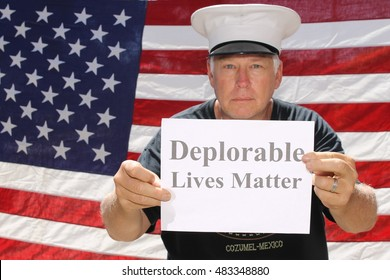 A man poses in front of am American flag with a Deplorable Lives Matter sign. With his dog.