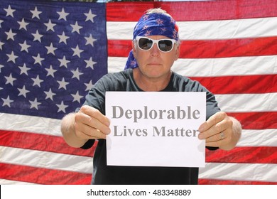 A man poses in front of am American flag with a Deplorable Lives Matter sign.With his dog.