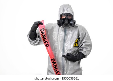A man poses in a gray protective suit with a hood on his head with a yellow radiation sign, with a protective gas mask, posing, standing on a white background, pointing to a red protective tape.