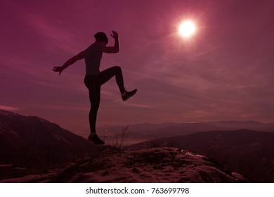 Man poses and jumps at snowy mountain