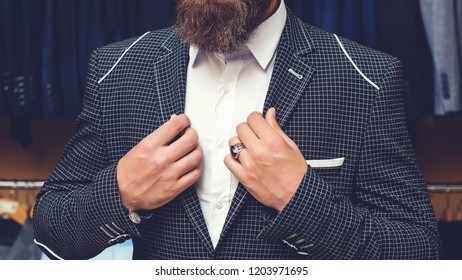 Man posing in black suit. Handsome brutal bearded man in stylish black jacket, white shirt inside of shopping mall. Representative suit. Men suit perfect to last detail. Advertising photo. Stylish.