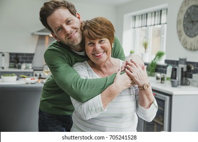 Man is posing for the camera with his mother at her home. He has his arms round her and they are both smiling for the camera.
