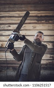 man posing with a chainsaw in a wooden house