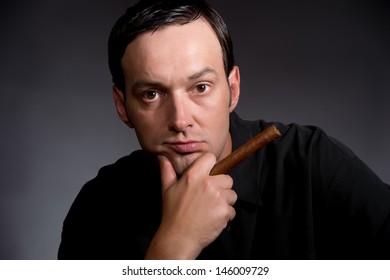 Man posing with cigar on black background closeup