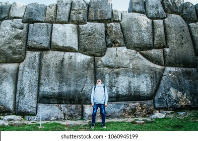Man posing in front of the huge rocks of Sacsayhuaman in Cusco - Peru
