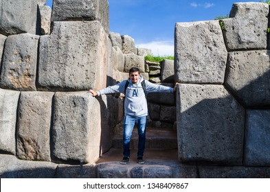 Man posing in front of the huge rocks of Sacsayhuaman in Cusco - Peru.