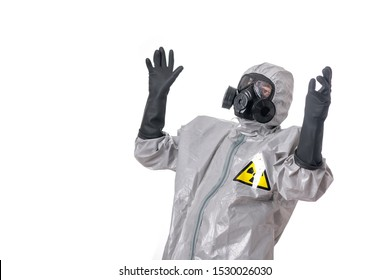 Man posing in a gray protective suit with a yellow radiation sign, with a protective gas mask, posing, standing on a white background.Isolated background. Raises arms up. Hazardous environment.