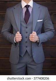 Man posing in grey suit