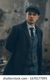 A man posing in the image of an English retro gangster of the 1920s dressed in a coat, suit and flat cap in Peaky blinders style.