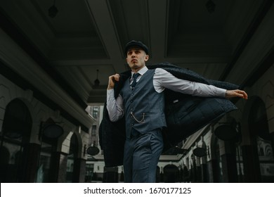 A man posing in the image of an English retro gangster of the 1920s dressed in Peaky blinders style at city street.