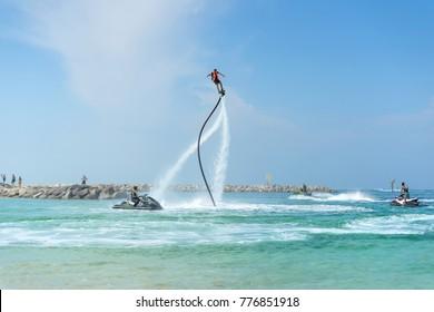 Man posing at new flyboard at Caribbean tropical beach. Positive human emotions, feelings, joy. Funny cute men making vacations and enjoying summer.