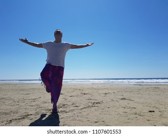man posing on the beach sand