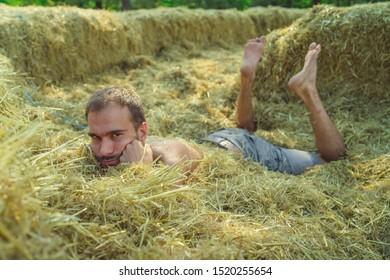 A man posing on a haystack. Casual man outdoor with haystack. attractive man laying on haystack