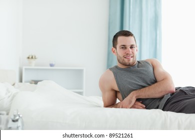 Man posing on his bed while looking at the camera