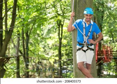 Man posing on platform at high rope course