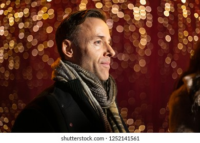 Man posing for photo in front of light wall at Christmas market.