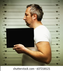man posing for police mugshot