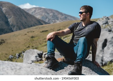 Man posing in profile sitting on a rock in Castle Hill. New Zealand trravel destination in the South Island