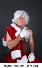 A man posing as Santa Claus is enjoying a cigar after a long Christmas day after removing his top.