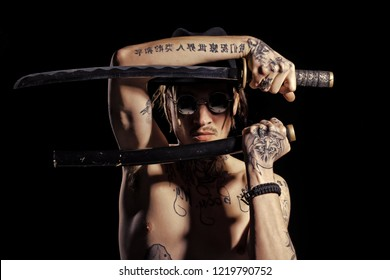 Man posing with sword with tattooed hands, neck and chest on black background. Defense, honor, torture, punishment, harakiri, tattoo concept.