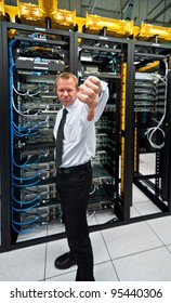 Man posing a thumbs-down in front of data center server racks.