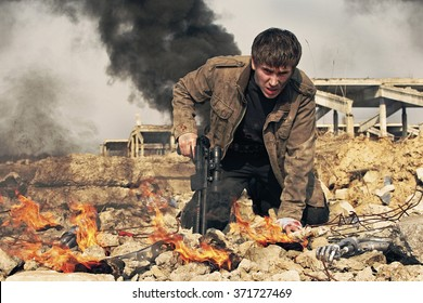 A man in a post-apocalyptic clothes kneeling with a shotgun amid the rubble and flames.