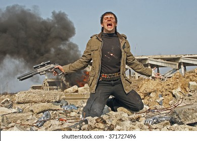 A man in a post-apocalyptic clothes kneels and cries among the debris on the background of the smoke and ruins.