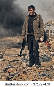 A man in a post-apocalyptic clothes with a shotgun in his hand standing amid the wreckage on a background of smoke and ruins.