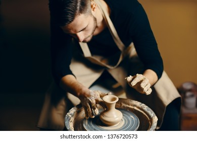 Man potter working on potters wheel making ceramic pot from clay in pottery workshop. art concept